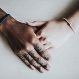 Multiracial couple clasp hands